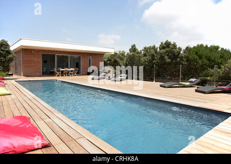 Lawn chairs and pool on modern deck - Stock Photo