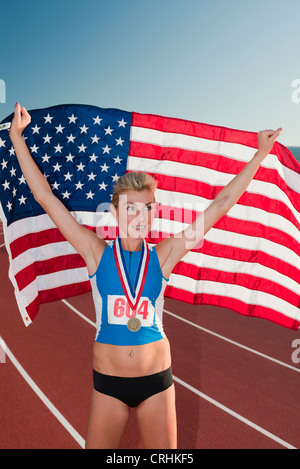 Female medal winner holding up American flag in victory - Stock Photo