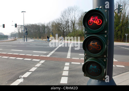 red bike traffic light with cyclists in the background, Germany - Stock Photo