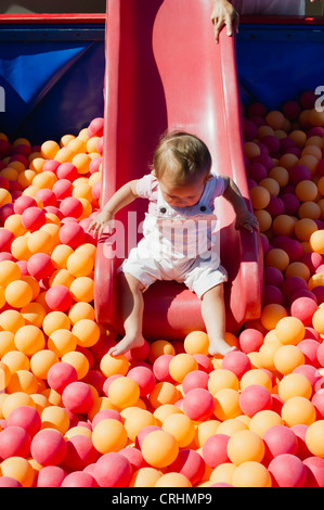 Toddler girl going down slide into ball pit on playground - Stock Photo
