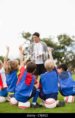Children raising hands during practice - Stock Photo