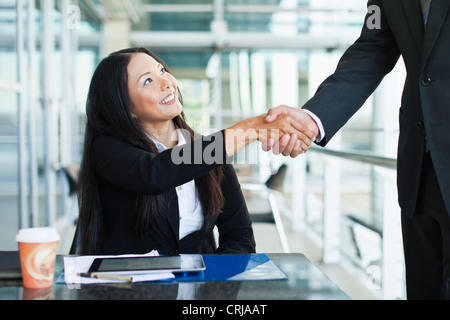 Business people shaking hands in cafe - Stock Photo