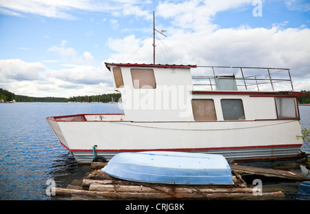 Small white boat moored on lake in Imatra town, Finland - Stock Photo