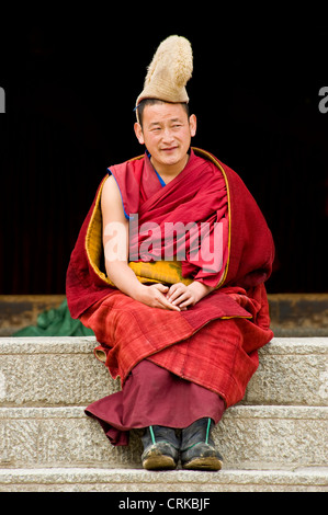 A Tibetan Buddhist monk (Geluk or Yellow Hat) outside the Grand Sutra Hall of the Labrang Monastery before going - Stock Photo