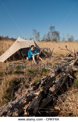 Hiker sitting by camp tent in tall grass - Stock Photo