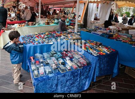 Young boy looking at model cars and lorries for sale at the market in Vieille Ville, Nice, Cote d'Azur, France - Stock Photo