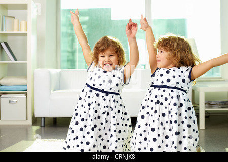 Adorable twin girls having fun together - Stock Photo