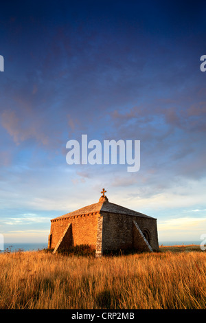 Sunrise over the thirteenth century square shaped St Aldhelm's Chapel near Worth Matravers. - Stock Photo