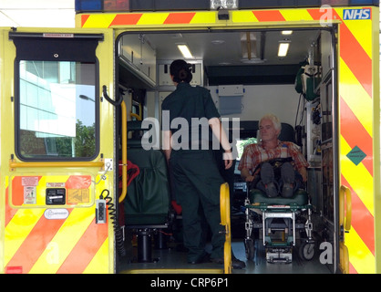 A male patient on trolley in the back of an NHS London ambulance with a paramedic by his side. - Stock Photo