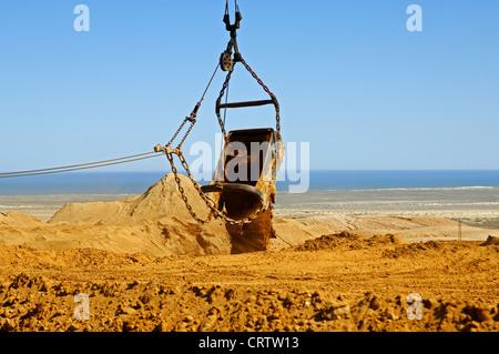 Dragline excavator dumping excavated material - Stock Photo