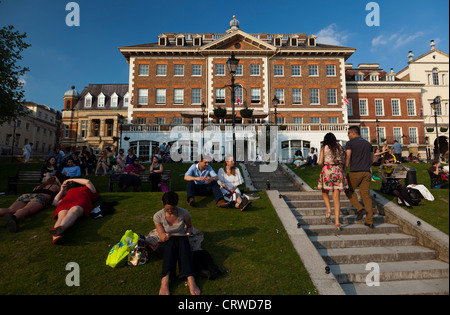 People sitting outdoors on summer afternoons on the grassy strip at the riverfront in Richmond in London. - Stock Photo