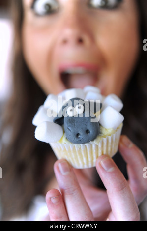 Home made Cupcake in the design of the Aardman childrens tv character Shaun the Sheep about to be bitten by young - Stock Photo