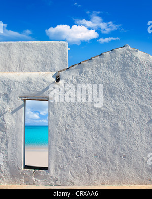 Balearic islands idyllic turquoise beach view through whitewashed house open door - Stock Photo