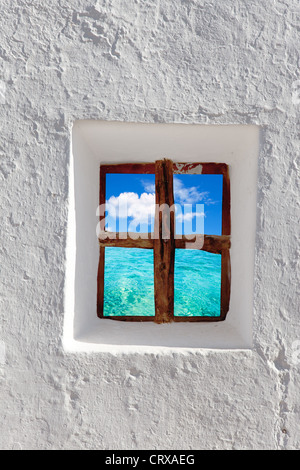 Balearic islands idyllic turquoise beach view through whitewashed house window - Stock Photo