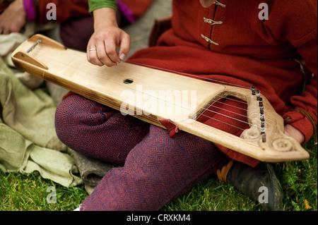 folk musician with gusli sitting on grass - Stock Photo