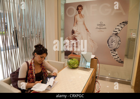 A young woman shopping for a watch in the Omega store, Westfield Shopping centre Stratford London UK - Stock Photo
