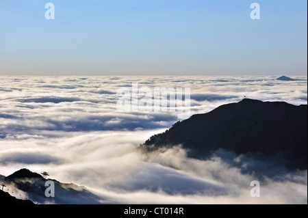 View over silhouetted chairlifts and mountains covered in mist at sunrise, Col du Tourmalet, Hautes-Pyrénées, Pyrenees, - Stock Photo