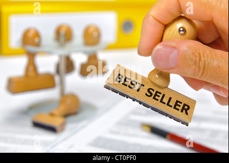 rubber stamp in hand marked with best seller - Stock Photo