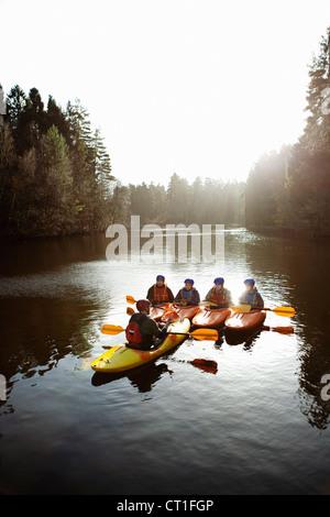 Teacher talking to students in kayaks - Stock Photo