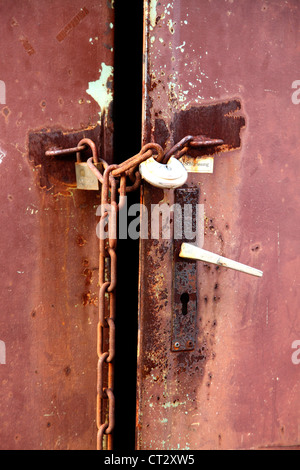 Red, rusty metal door, locked with an iron chain. - Stock Photo