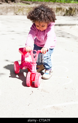 Girl playing with tricycle in park - Stock Photo