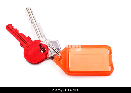Red door key and silver car key on keyring with orange tag for writing on, on white with soft shadow. - Stock Photo
