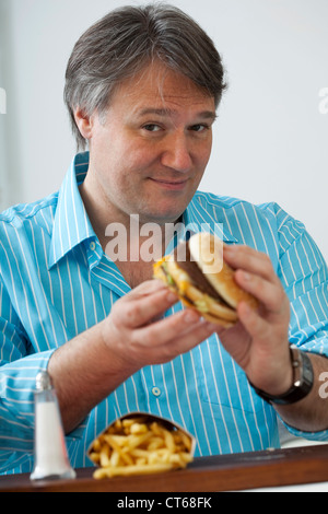 MAN EATING A SANDWICH - Stock Photo