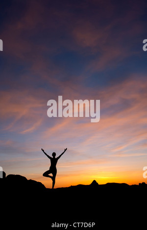 Young woman doing yoga in desert, silhouette - Stock Photo