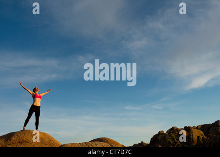 Young woman standing in desert with arms open - Stock Photo