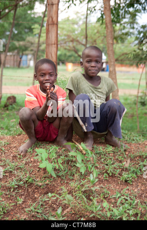 Two young Kenyan boys sit by the road side. - Stock Photo