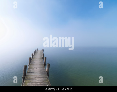 Wooden jetty in fog at lake Chiemsee, Frauenchiemsee, Chiemgau, Bavaria, Germany - Stock Photo