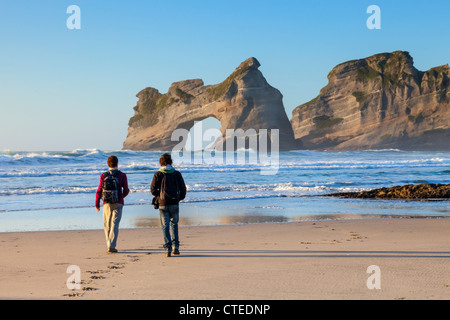 Two visitors walking on Wharariki Beach in the Tasman Region of New Zealand in the evening. - Stock Photo