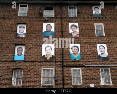 Faces upon the windows of a no longer occupied housing estate awaiting demolition in Hackney,London. - Stock Photo