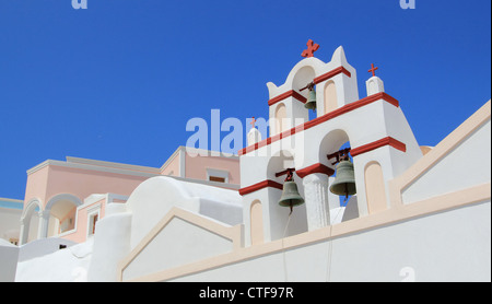 Close up of a white and red belfry of a typical greek church behind colorful houses by beautiful weather, Oia, Santorini, - Stock Photo