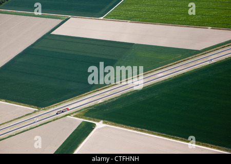 The Netherlands, Dronten, Truck and car on road in Flevopolder. Aerial. - Stock Photo