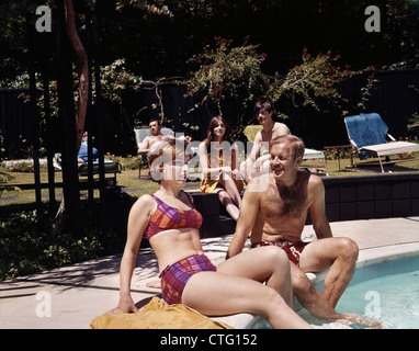 1960s FOUR PEOPLE ON PATIO COUPLE MAN WOMAN SITTING ON EDGE OF SWIMMING POOL - Stock Photo