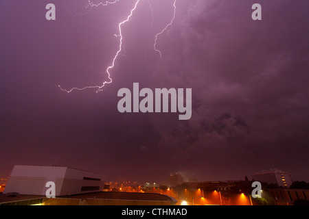 Lightning illuminates the sky purple during a thunderstorm over a city, accompanied by heavy rain and haze (visible - Stock Photo