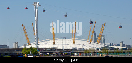 Emirates Air Line cable cars seen in front of The O2 arena dome viewed from Royal Docks crossing River Thames linking - Stock Photo