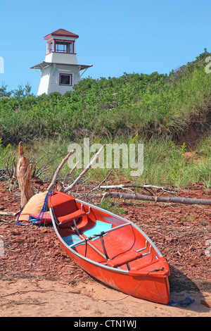 A canoe and some driftwood laying on the beach in front of the lighthouse at Cabot Beach in Malpaque, Prince Edward - Stock Photo