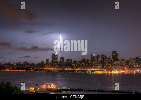 Lightning bolts illuminate the night sky over the upper west side skyline during a summer thunderstorm in New York - Stock Photo