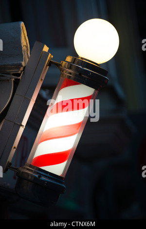 An old fashioned red and white striped barbers pole - Stock Photo