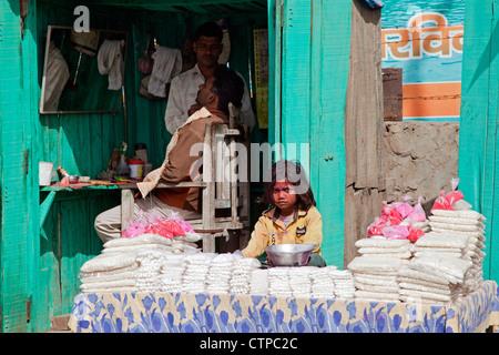 Hairdresser cutting hair in barbershop and child behind display selling goods in Govardhan, Uttar Pradesh, India - Stock Photo