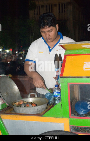 local man selling fresh sea food at his stall at the night market batavia old town jakarta java indonesia - Stock Photo