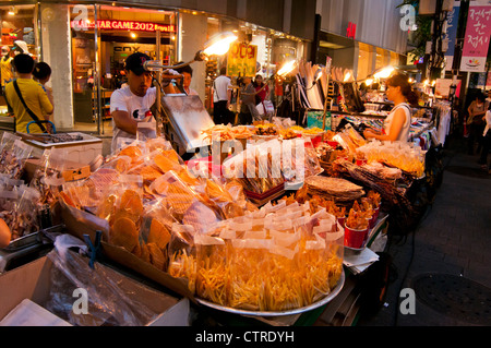 Street food stalls selling various foods and snacks in the evening in the popular shopping district of Myeongdong - Stock Photo