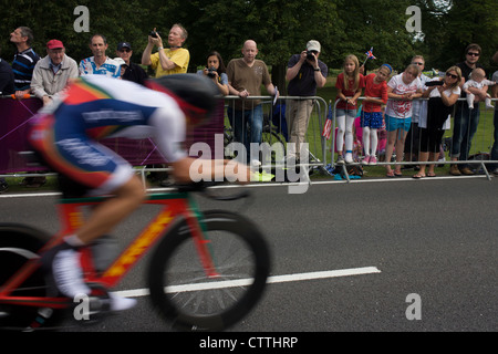 A cyclist races past fans lining the route through Bushy Park in south west London, during the London 2012 Olympic - Stock Photo