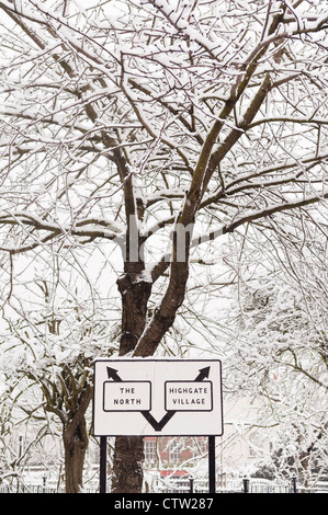Road sign in Highgate, with snow-covered trees in the background. - Stock Photo