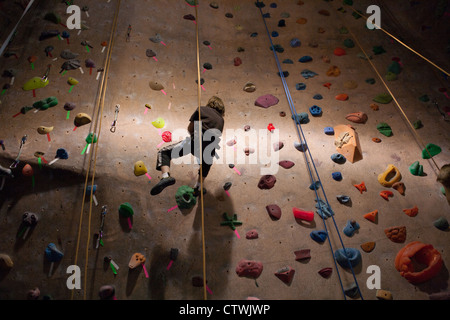 Boy coming down from a climbing wall. - Stock Photo