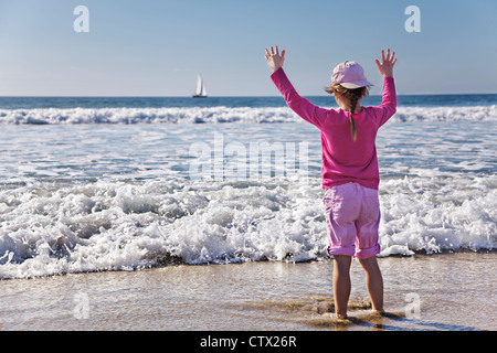 Young girl holds up hands as wave approaches her - Stock Photo