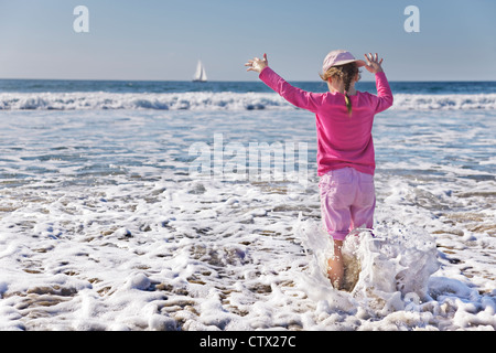 Young girl gets wetter than she planned as a wave soaks her - Stock Photo