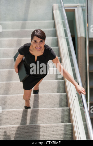 Hispanic businesswoman going up stairs of office building - Stock Photo